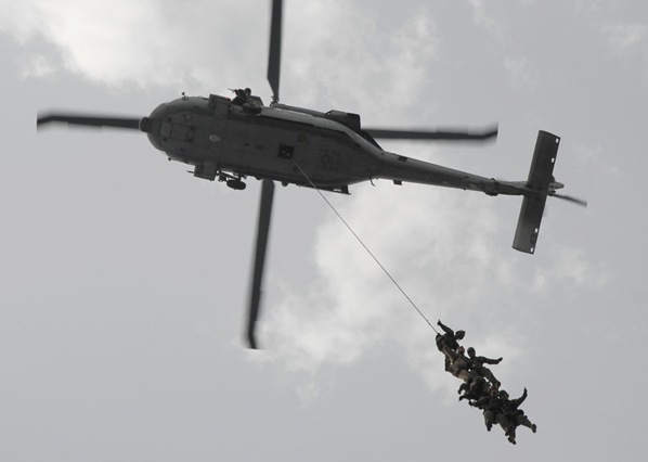 PERSIAN GULF (May 9, 2008) Members of the helicopter visit, board, search and seizure team of the aircraft carrier USS Abraham Lincoln (CVN 72) perform a helicopter rope suspension maneuver out of an MH-60 Seahawk helicopter over the flight deck of the amphibious assault ship USS Nassau (LHA 4) during a training exercise. U.S. Navy photo by Mass Communication Specialist 3rd Class Coleman Thompson (RELEASED).